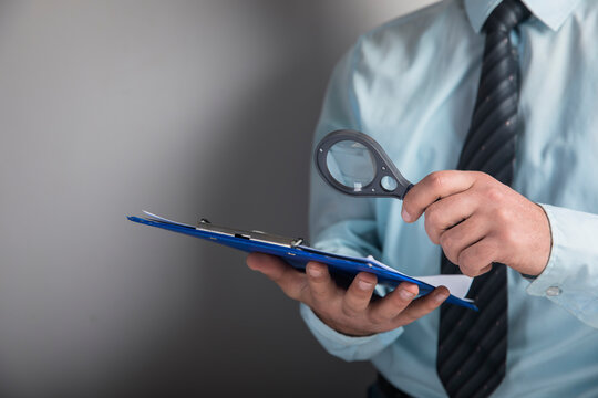magnifying glass looks at documents