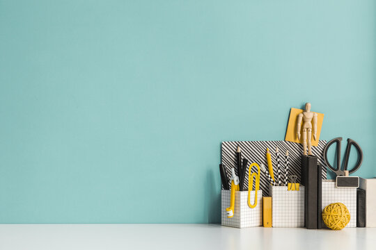 Creative desk with a blank picture frame, desk objects, drawing supplies, pencils, brushes, near bright pastel wall. Artist workspace.