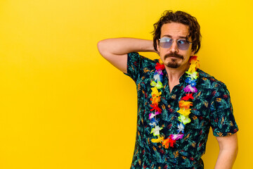 Fototapeta Young caucasian man wearing a hawaiian necklace isolated on yellow background touching back of head, thinking and making a choice.