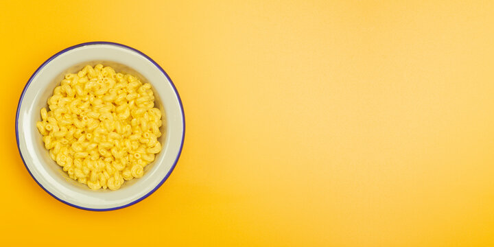 Pasta banner background. Mac and Cheese pasta on a yellow background. American style Italian pasta with cheese.