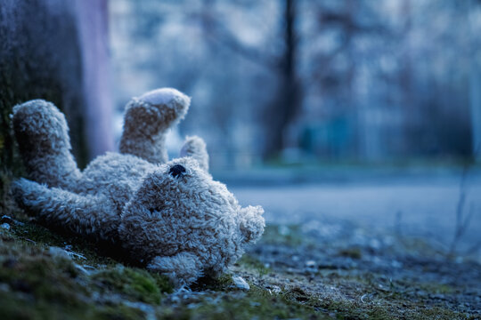 Lost childhood concept. Dirty teddy bear lying down outdoors. Copy space for text or design.