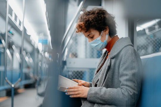 woman in a protective mask reads a book on a subway train.