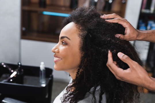 Side view of smiling african american client sitting near hairstylist touching hair