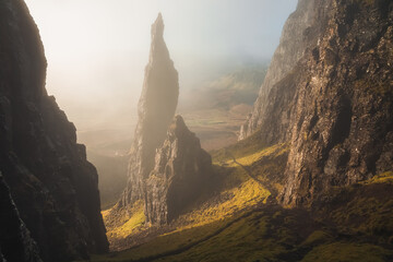 Fototapeta Moody, atmospheric fog and mist with golden sunrise or sunset light and shadow at the iconic Needle rock pinnacle at the Quiraing on the Trotternish Ridge, Isle of Skye.