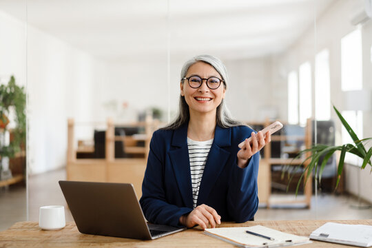 The smiling Asian woman holding a phone in her hand in a light office
