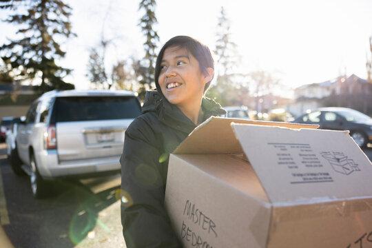 Teenage girl carrying cardboard box in sunny parking lot