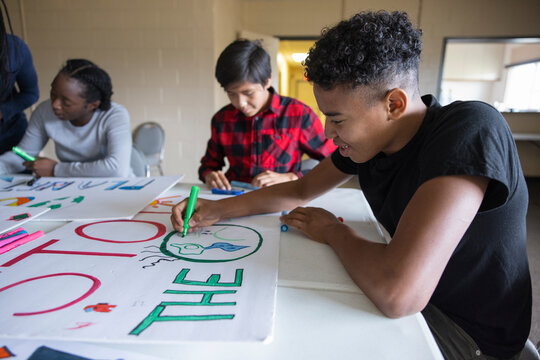 Teen activists coloring environmental posters in community center