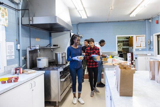 Volunteers preparing sack lunch sandwiches in community center kitchen