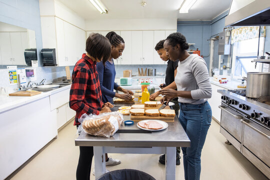 Volunteers making ham sandwiches in community center kitchen