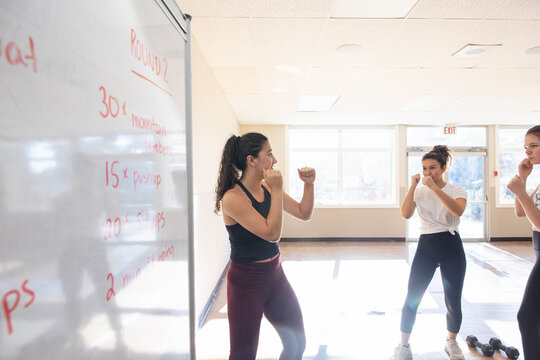 Teen boxing instructor teaching class in sunny gym studio