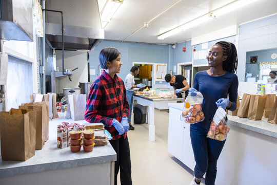 Volunteers preparing sack lunches in community center kitchen
