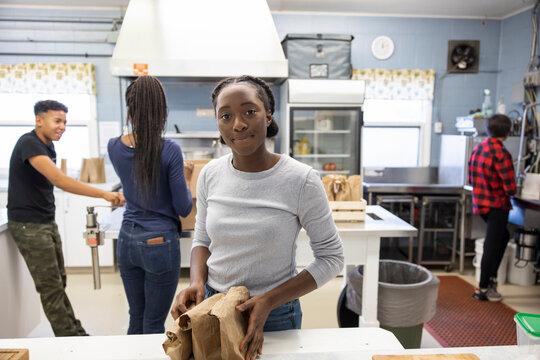Portrait confident teen girl volunteering in community center kitchen