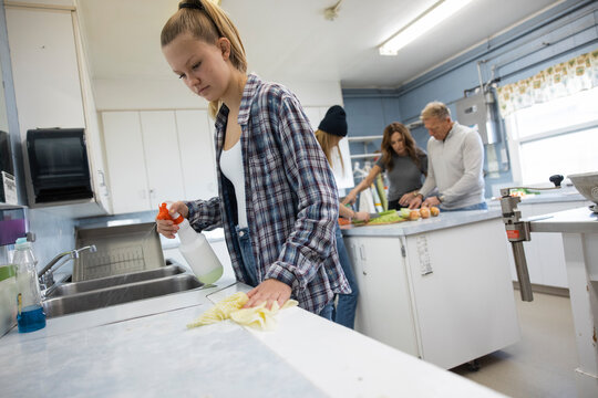 Family volunteers cooking and cleaning community center soup kitchen