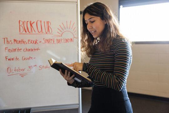 Teen girl reading aloud at whiteboard in book club meeting