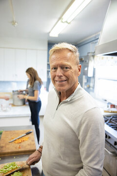 Portrait confident mature man volunteering in soup kitchen