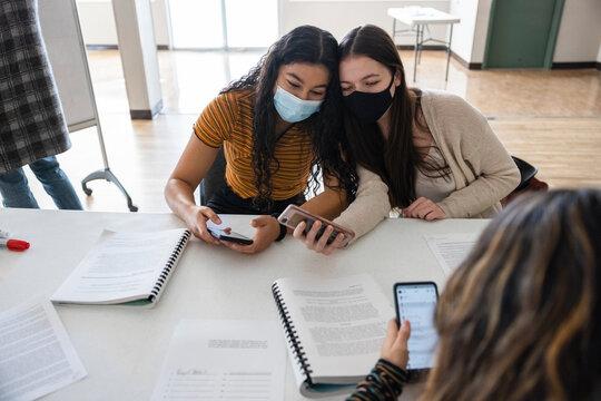 Happy teen girl friends in face masks taking selfie in classroom