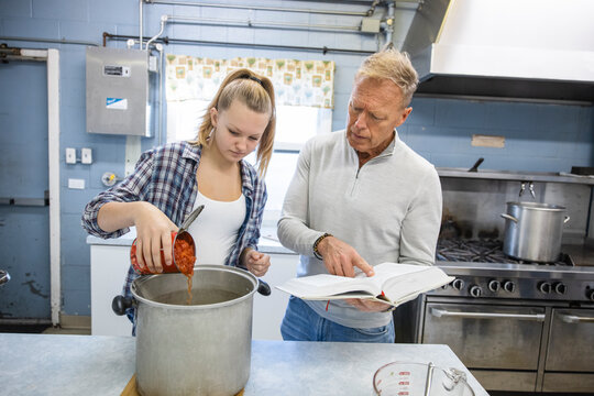Father and daughter volunteers cooking in soup kitchen