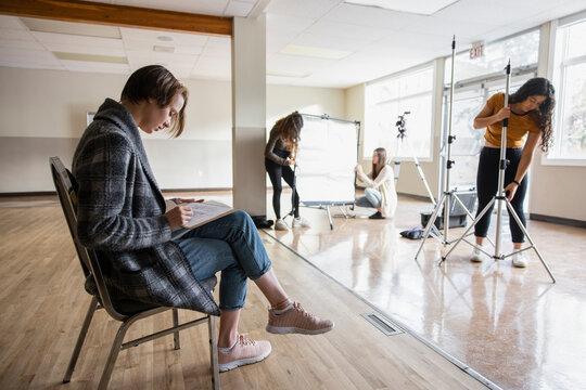 High school girl students preparing photographic equipment in studio