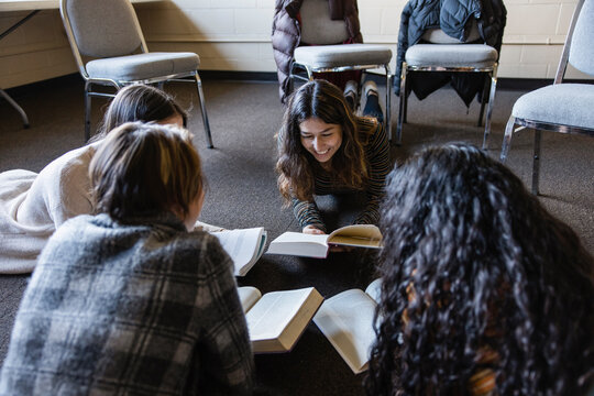 Happy teen girls reading in circle on floor at book club meeting