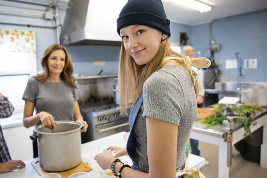 Portrait confident teen girl volunteering with family in soup kitchen