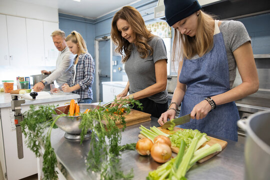 Family volunteers cutting fresh vegetables in soup kitchen