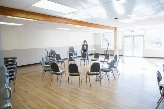 Girl volunteer in face mask arranging chairs in community center