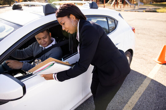 Driving instructor with clipboard talking to student in parked car