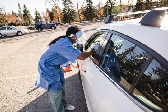 Nurse in PPE taking COVID-19 test at car window in parking lot