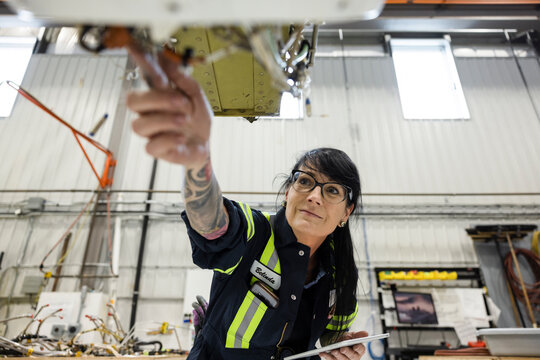 Woman assembling part of helicopter