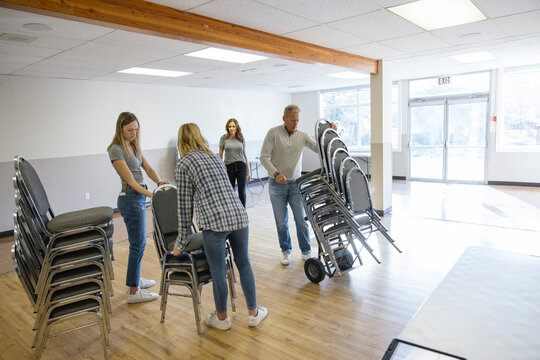 Family volunteers arranging chairs in community center