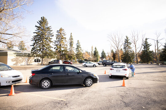 Cars waiting for drive thru COVID-19 test in sunny parking lot