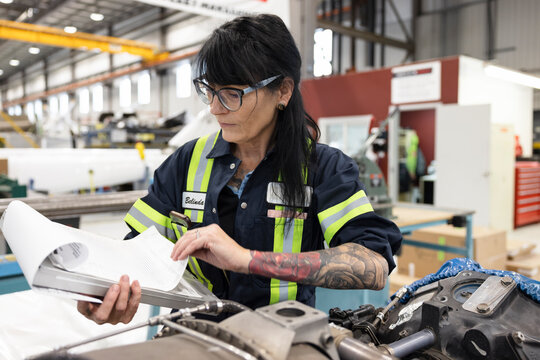 Woman working on helicopter component