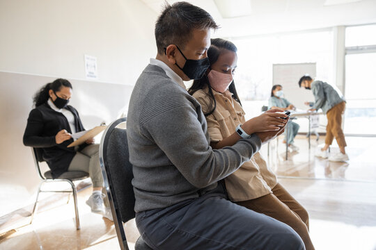 Father and daughter in face masks waiting in clinic with smart phone