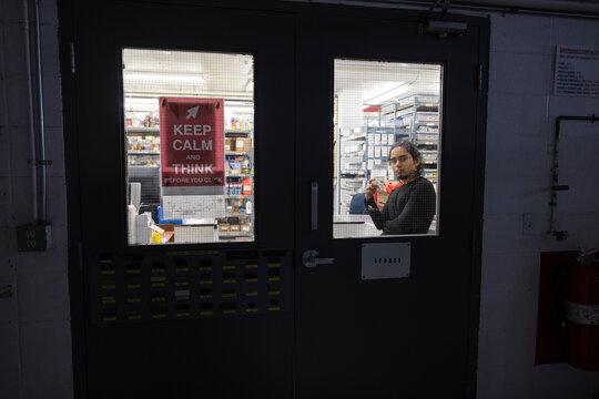 Technician in storeroom seen through window