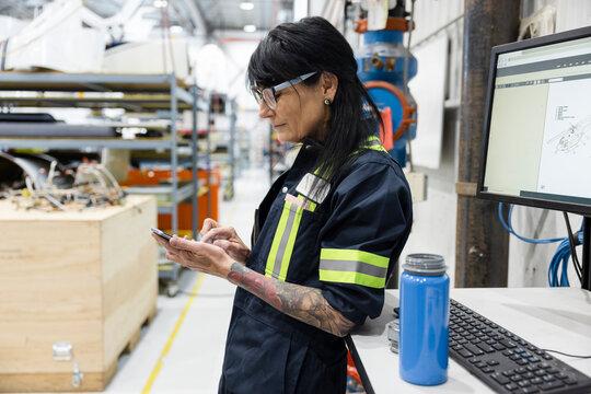 Technician taking break looking at phone in helicopter hangar