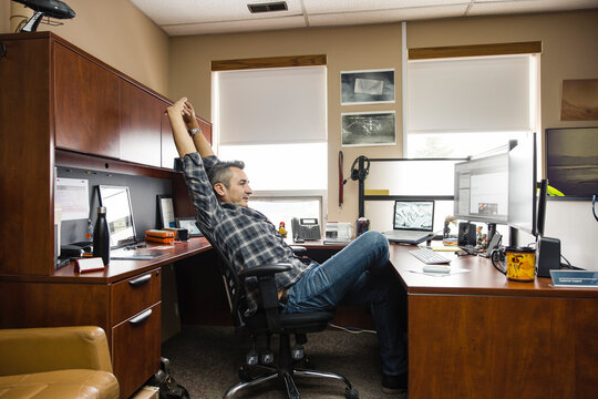 Man sitting stretching at desk in office