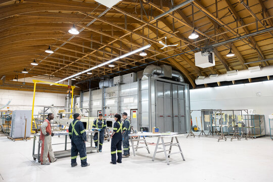 Technicians having a standing meeting in helicopter hangar
