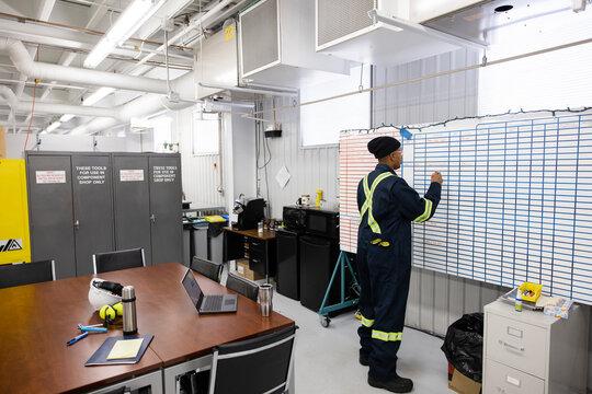 Technician filling in wall planner