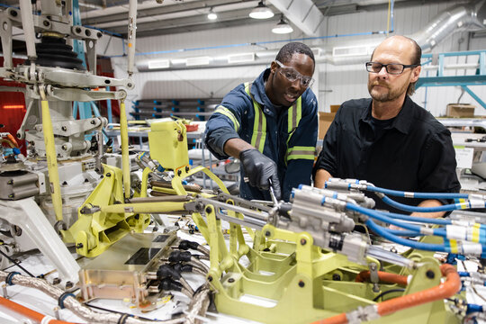 Engineers working on helicopter component