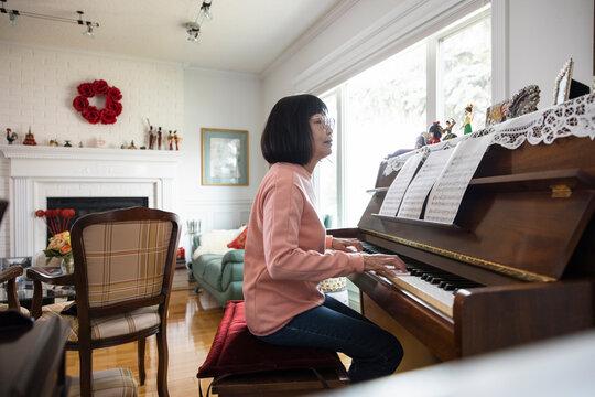Senior woman playing piano at home