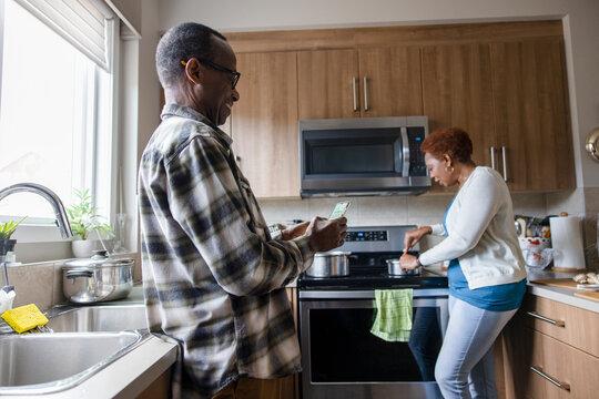 Senior man texting on phone in kitchen