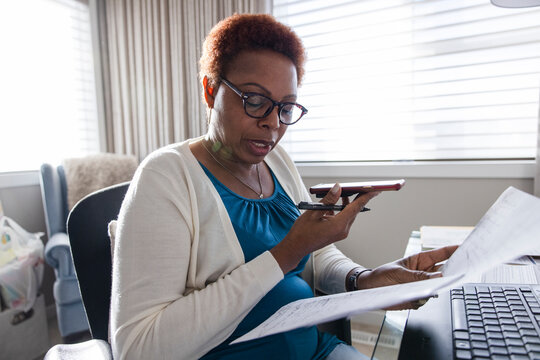 Senior woman working with phone in home office