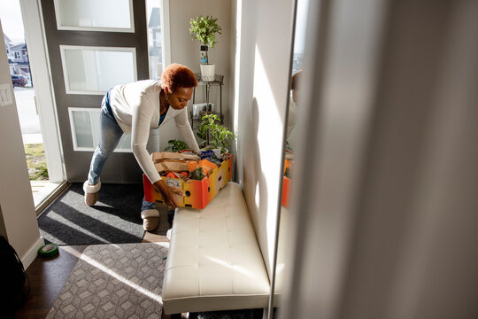 Senior woman placing box of groceries on bench