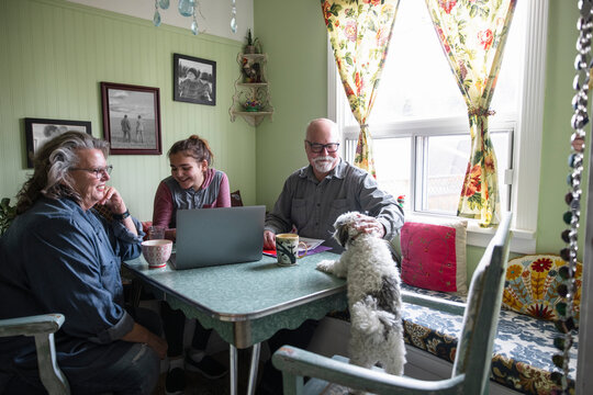 Grandparents and granddaughter relaxing with pet dog at home