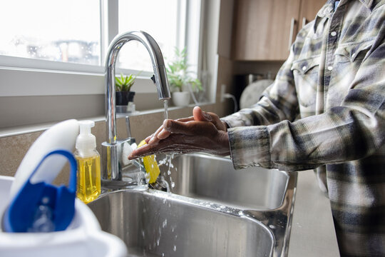 Man washing hands in kitchen sink