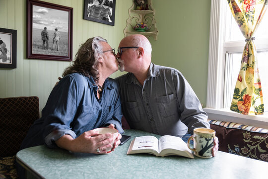 Portrait of senior couple kissing at dining table