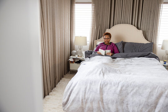 Senior woman relaxing in bed reading book