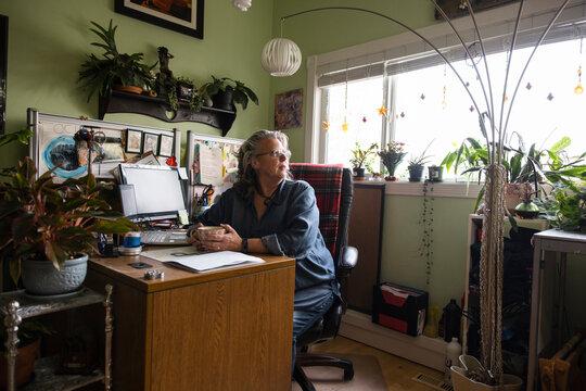 Senior woman taking break in home office