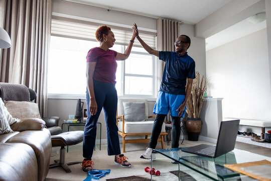 Senior couple giving highfive at home
