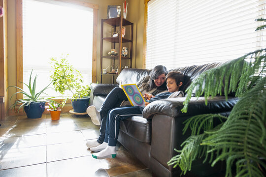 Woman with down syndrome reading with nephew on sofa